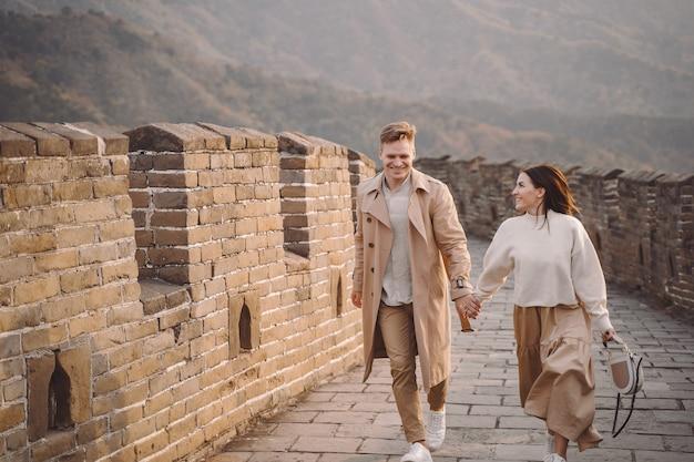 Jong paar dat en bij de grote muur van china loopt tolt