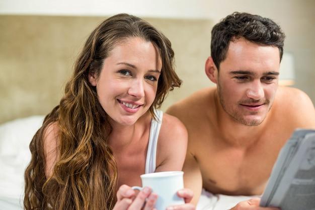 Jong paar dat en een krant op bed ontspant leest