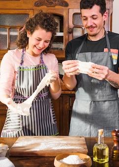 Jong paar dat gekneed deeg in de keuken bekijkt