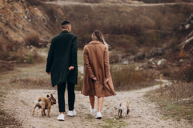 Jong paar dat hun franse buldoggen in park loopt