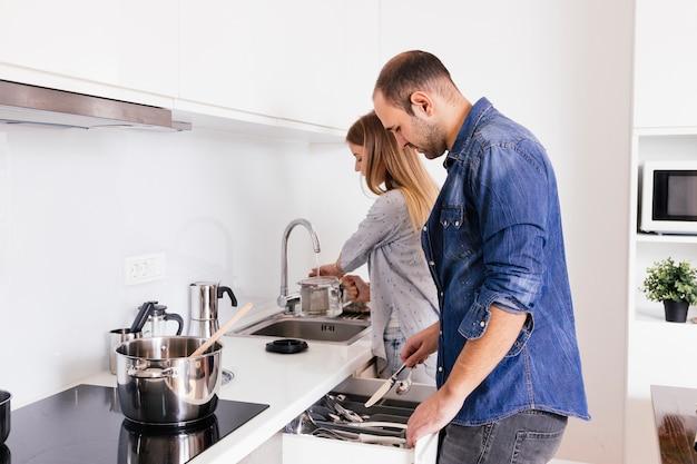 Jong paar dat met werktuigen in de keuken werkt