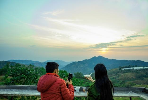 Jong paar dat mooi zonsopgangogenblik op de berg kijkt