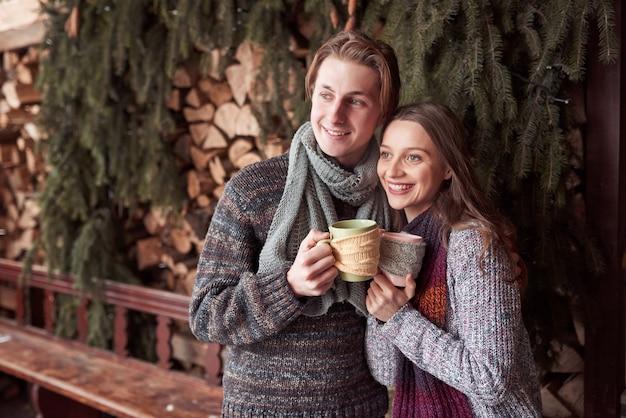 Jong paar dat ontbijt in een romantische cabine in openlucht in de winter heeft. wintervakantie en vakantie. kerst paar gelukkige man en vrouw drinken warme wijn. verliefd stel