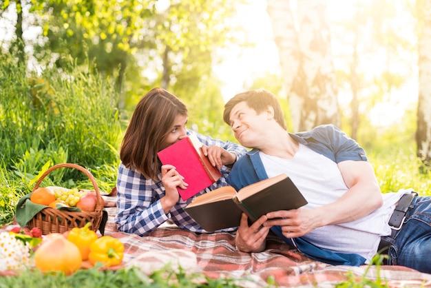 Jong paar dat op deken ligt en boeken leest