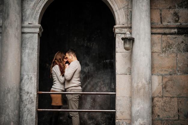 Jong paar dat op gebonden warme sweaters draagt die in liefde bij oude werf met boog en kolommen bij stad koesteren.
