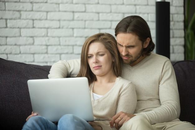 Jong paar dat op laptop met afschuw kijkt die door nieuws wordt verward