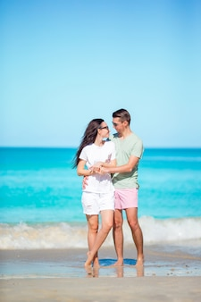 Jong paar dat op tropisch strand met wit zand en turkoois oceaanwater bij het eiland van antigua in de caraïben loopt