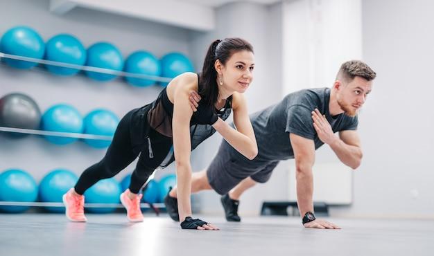 Jong paar dat opdrukoefeningen van vloer één hand samen doet