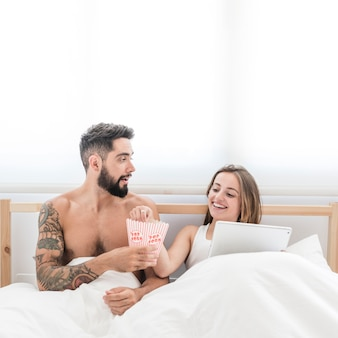 Jong paar dat popcorn op bed eet
