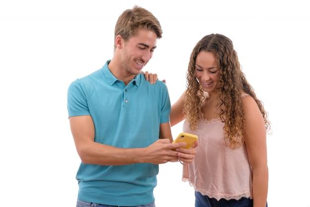 Jong paar dat pret heeft en met hun mobiele telefoon lacht die op witte achtergrond wordt geïsoleerd