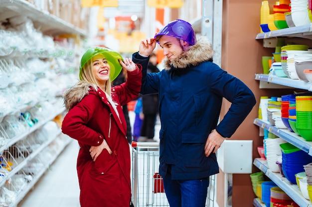 Jong paar dat rond met kommen in een supermarkt voor de gek houdt