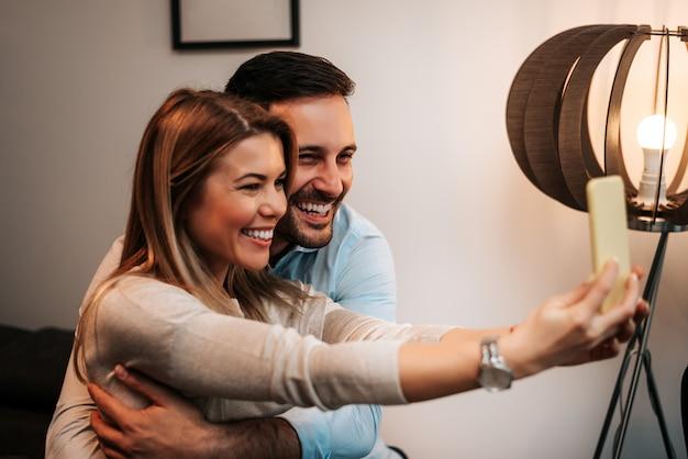 Jong paar dat selfies met haar smartphone in hun huis neemt.