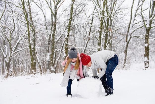 Jong paar dat sneeuwman in bos maakt