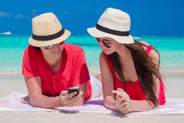Jong paar dat telefoon bekijkt die op tropisch strand ligt