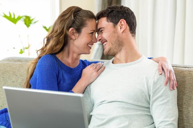Jong paar dat van aangezicht tot aangezicht op bank glimlacht en laptop in woonkamer met behulp van