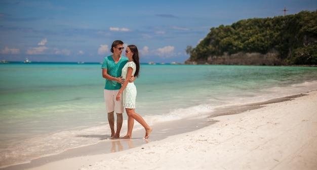 Jong paar dat van elkaar op zandig wit strand geniet
