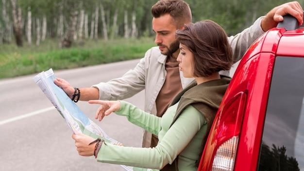 Jong paar dat zich dichtbij auto bevindt die op kaart kijkt