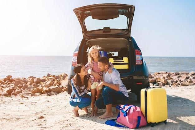 Jong paar dat zich dichtbij de geopende autolaars bevindt met koffers en zakken. vader, moeder en dochter reizen door de zee of de oceaan of de rivier. zomerrit met de auto