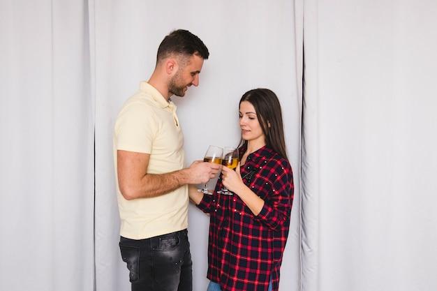 Jong paar dat zich voor gordijn bevindt dat de wijnglazen rammelt
