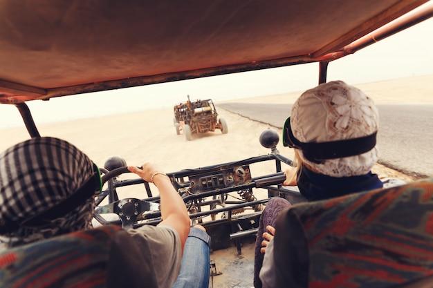 Jong paar die auto met fouten in woestijn berijden
