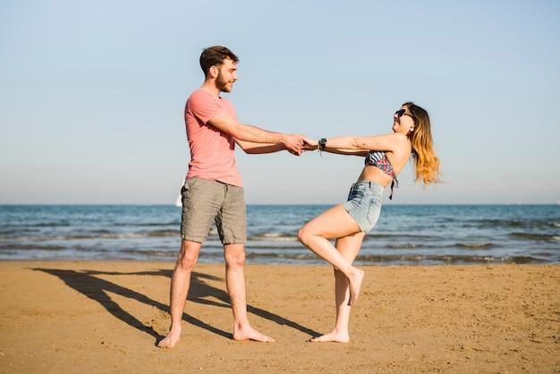 Jong paar die bij dichtbijgelegen de zeekust dansen bij strand tegen blauwe hemel