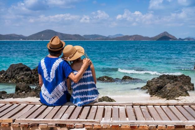 Jong paar die en bij het tropische strand, de zomervakantie en het reisconcept ontspannen genieten van
