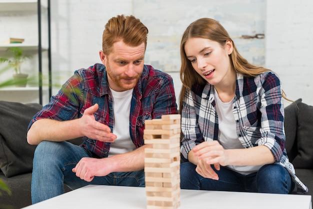 Jong paar die uit het houten de torenspel van de stapel op tafel kijken
