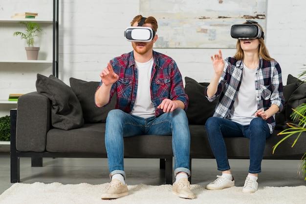 Jong paar die virtuele werkelijkheidsbeschermende brillen dragen die in de lucht met handen betrekking hebben