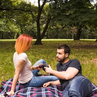 Jong paar die wijnglazen roosteren op deken over het groene gras