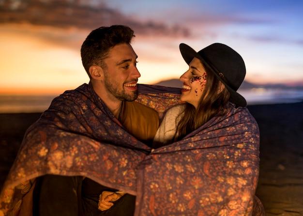 Jong paar in deken die op overzeese kust lachen