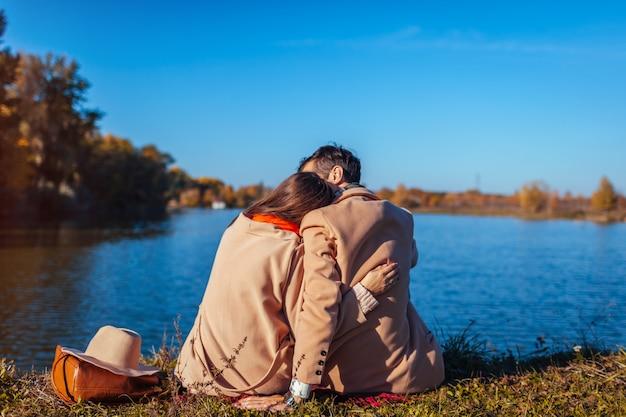Jong paar in liefde chillen door herfst meer en knuffelen