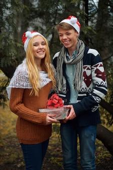 Jong paar in liefde die kerstmanhoeden dragen en een gift houden