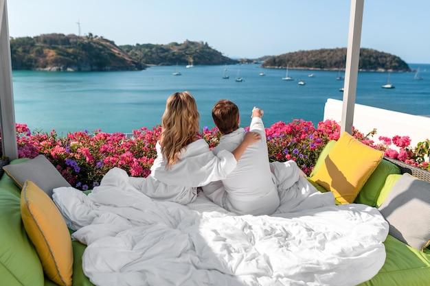 Jong paar in liefde knuffelen op een bed over de aard van een resorthotel. geniet van het uitzicht op zee en de jachten