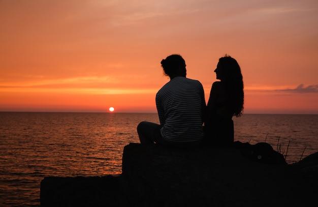 Jong paar in liefde tegen zonsondergang op zee