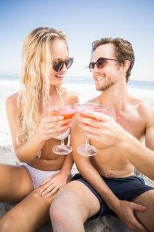 Jong paar in zonnebril die cocktailglas op het strand roosteren
