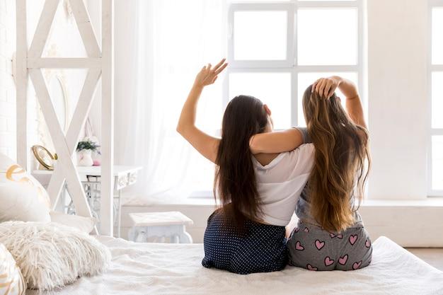 Jong paar knuffelen en zittend op het bed