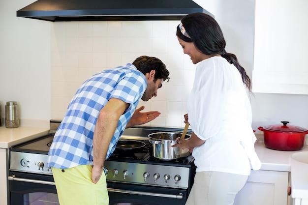 Jong paar kokend voedsel samen in keuken