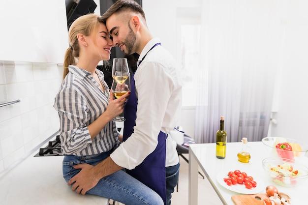 Jong paar met wijnglazen die in keuken koesteren