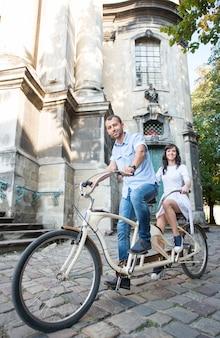 Jong paar op retro fiets achter elkaar bij de straatstad