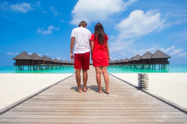 Jong paar op tropische strandpier bij perfect eiland