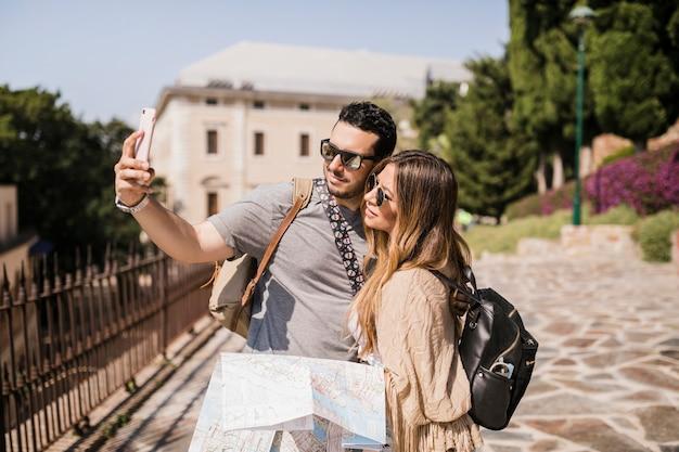 Jong paar op vakantie die zelfportret met celtelefoon neemt