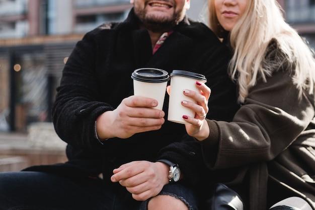 Jong paar verliefd buiten. reizigers met kopjes koffie lopen in het lentepark. mooie zonnige dag. een jong stel dat koffie drinkt om te gaan