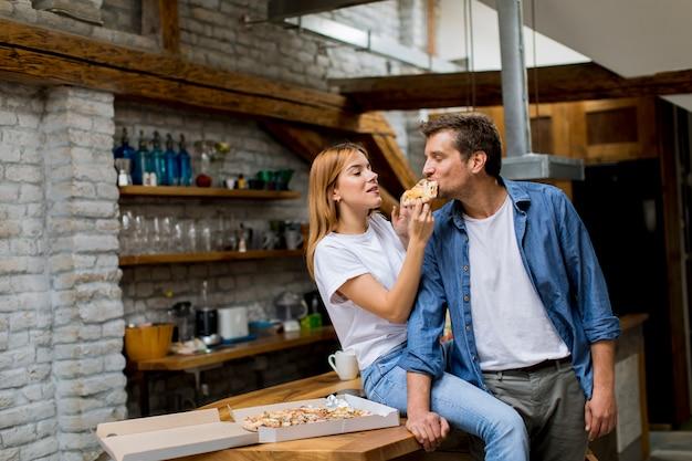 Jong paar verliefd pizza eten in het rustieke huis