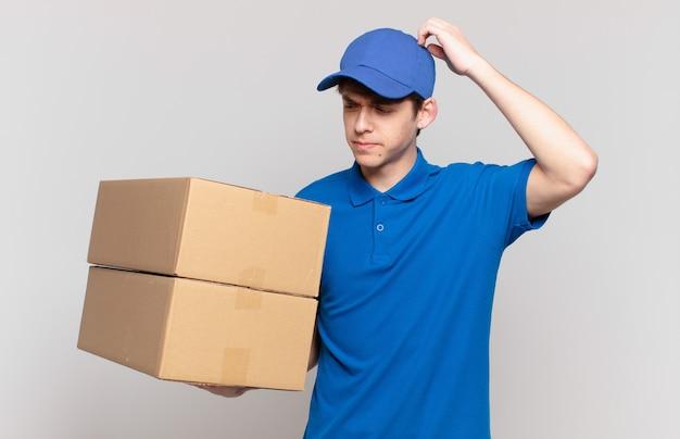 Jong pakket bezorgt jongen die zich verbaasd en verward voelt, hoofd krabt en opzij kijkt
