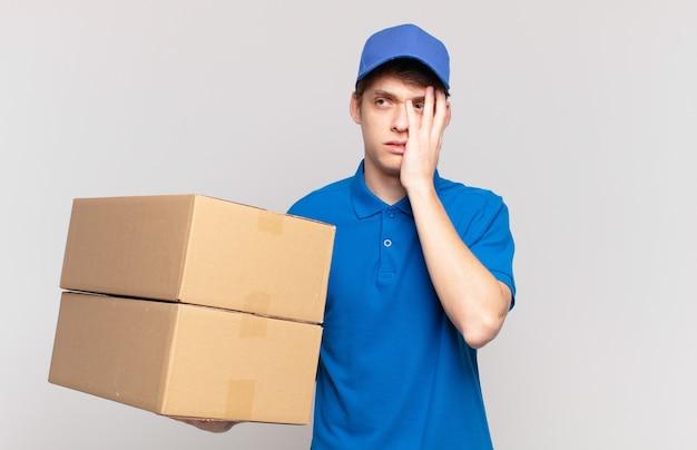 Jong pakket bezorgt jongen die zich verveeld, gefrustreerd en slaperig voelt na een vermoeiende, saaie en vervelende taak, gezicht met de hand vasthoudend