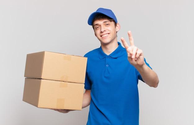 Jong pakket bezorgt jongen glimlachend en ziet er gelukkig, zorgeloos en positief uit, gebarend overwinning of vrede met één hand