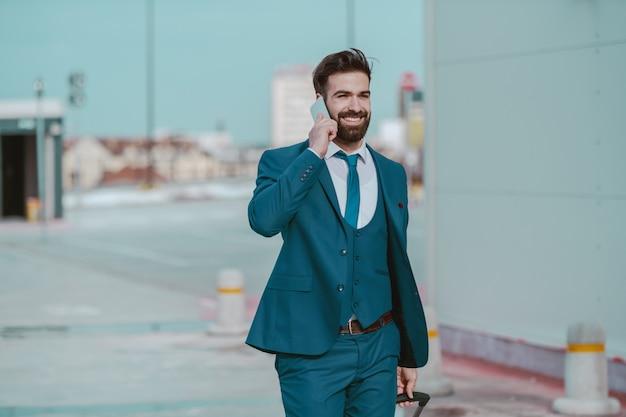 Jong perspectief die gebaarde kaukasische zakenman in formele slijtage glimlachen die op de telefoon spreken terwijl het dragen van bagage en het lopen op de parkeerplaats. bedrijfsconcept reis.