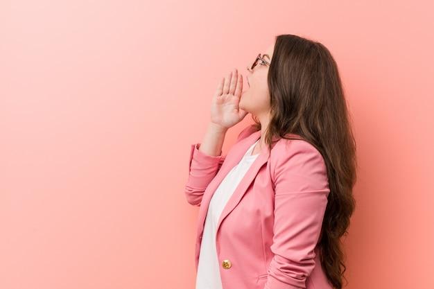 Jong plus grootte bedrijfs kaukasische vrouw die en palm schreeuwen houden dichtbij geopende mond.