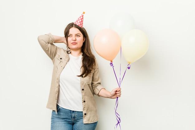 Jong plus size bochtige vrouw die een verjaardag viert wat betreft achterkant van hoofd, denkt en een keuze maakt.