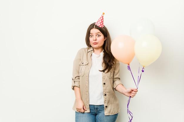 Jong plus size bochtige vrouw viert een verjaardag haalt schouders op en verwarde ogen open.